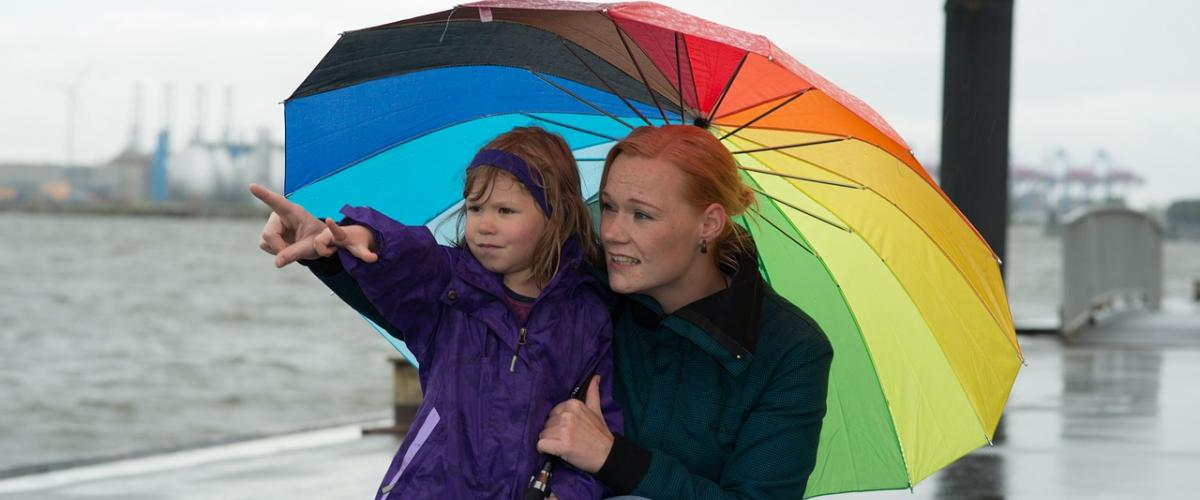 Eine Mutter und ein Kind benutzen einen bunten Regenschirm, um sich vor Regen zu schützen