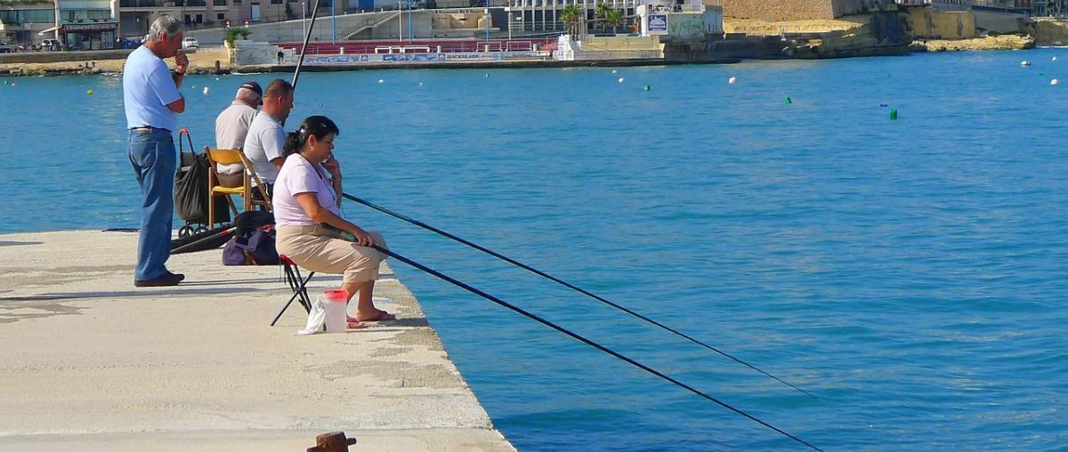 Angler mit Anglerausrüstung sitzen auf einem Anglerhocker und warten auf einen Fang