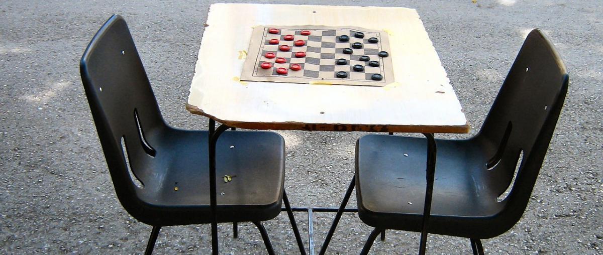 Dame-Brettspiel mit roten und schwarzen Spielsteinen auf einem Tisch im Freien und mit zwei Stühlen