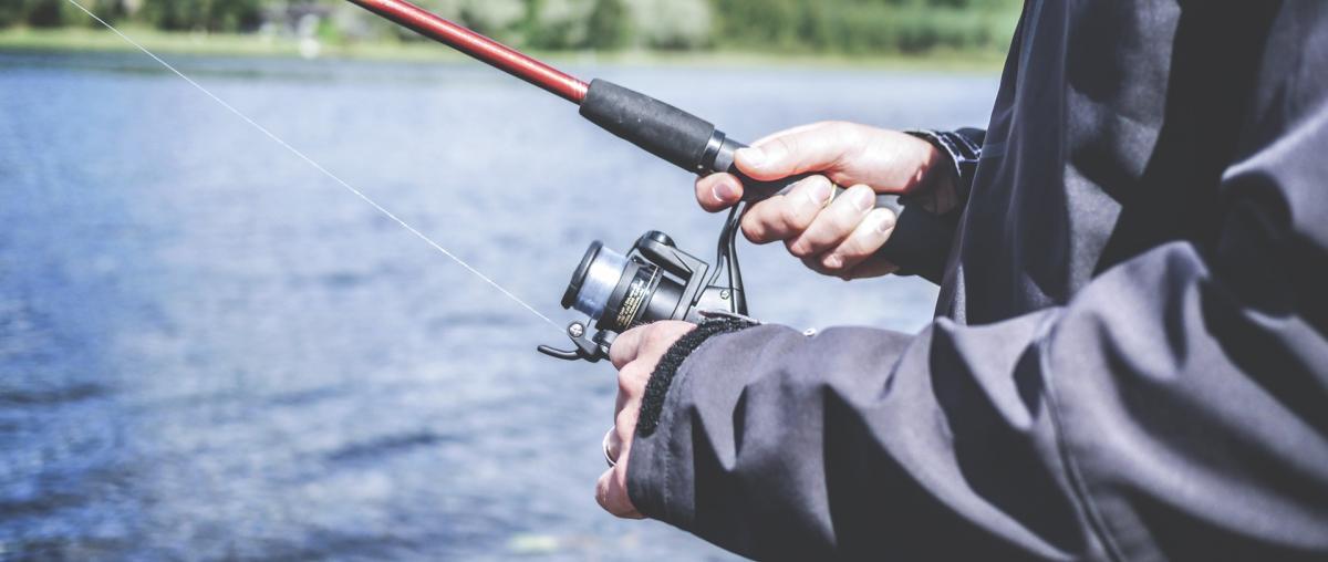 Fischer mit Angelrolle, die an einer Angelrute angebracht ist