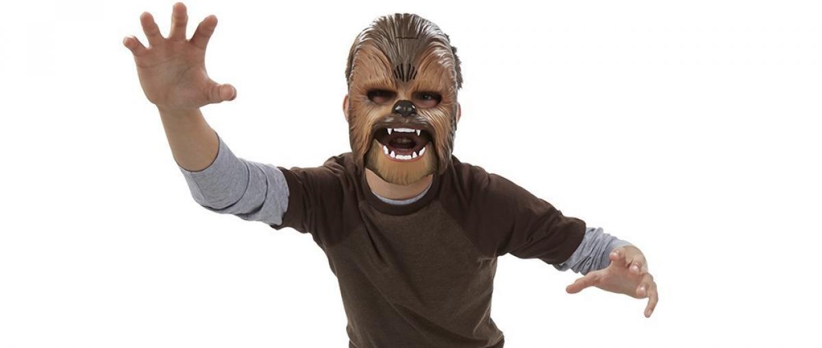 Kind mit Chewbacca-Maske auf dem Kopf macht eine Pose