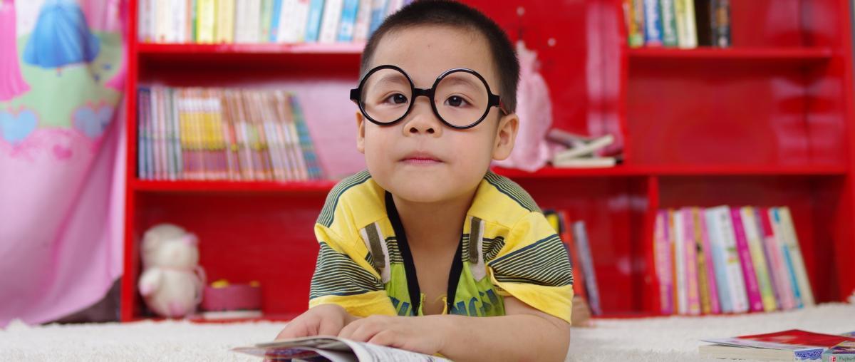 Kind mit runder Brille mit schwarzem Gestell liest ein Buch auf einem Teppich