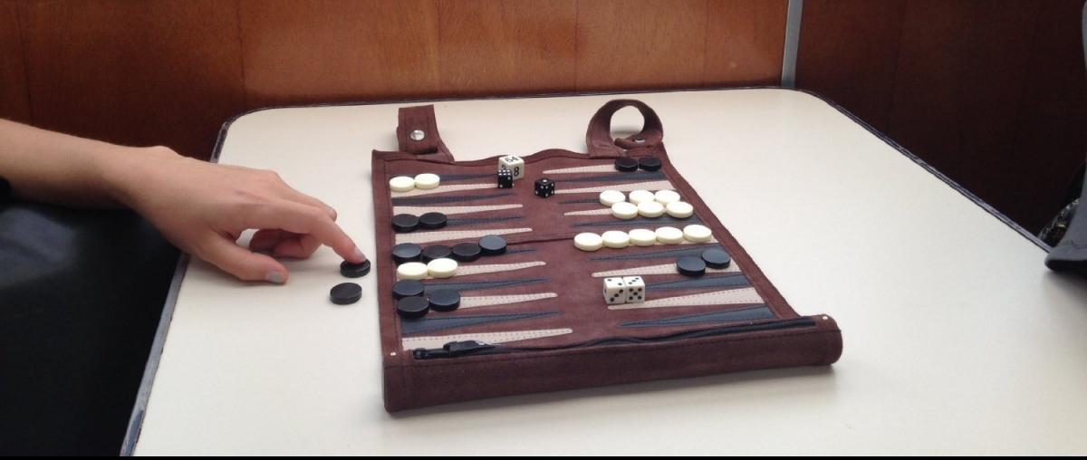 Portables Backgammon-Spiel mit schwarzen und weißen Spielsteinen und Würfeln und Dopplerwürfel