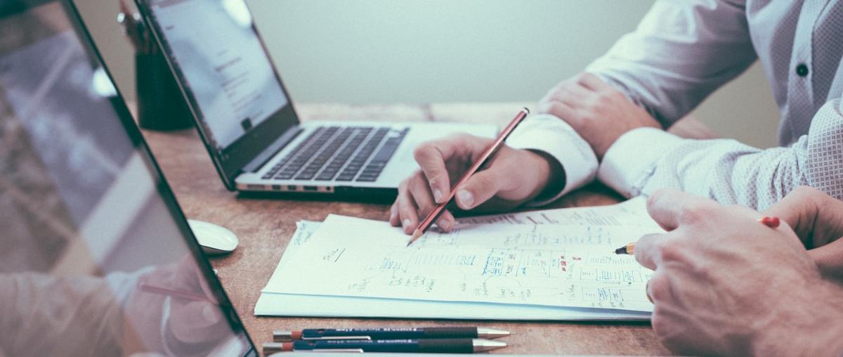 Zwei Personen bei einem Treffen mit Notebooks, Stiften und Papier
