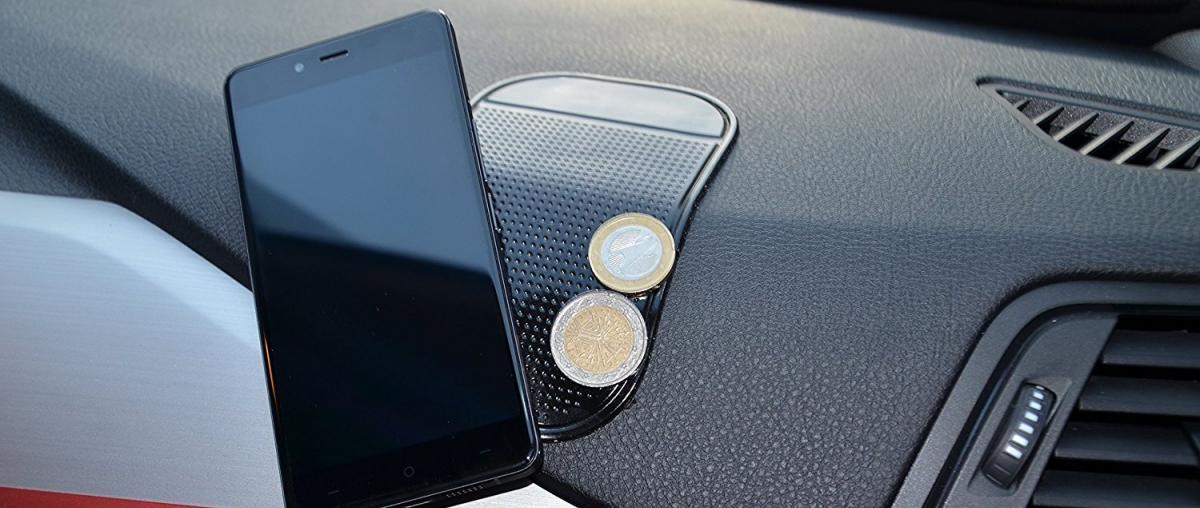 Angebrachtes Antirutsch-Pad am Armaturenbrett eines Autos mit Handy und Münzen