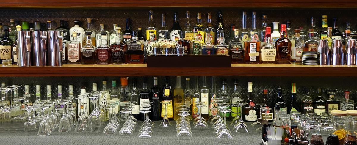 Bar mit verschiedenen Gläsern und Flaschen Alkohol