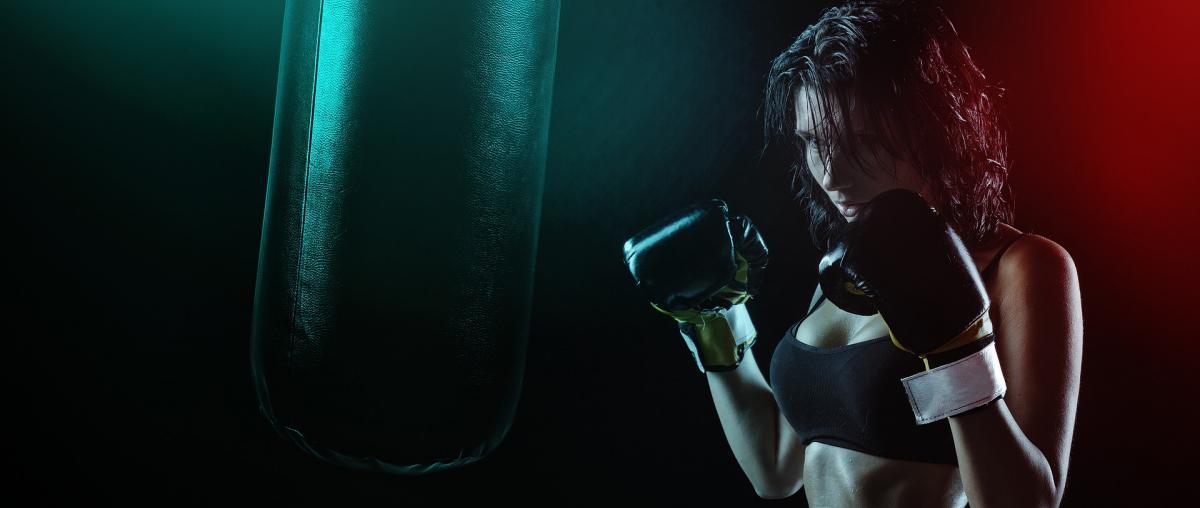 Frau mit Boxhandschuhen beim Training mit einem Boxsack