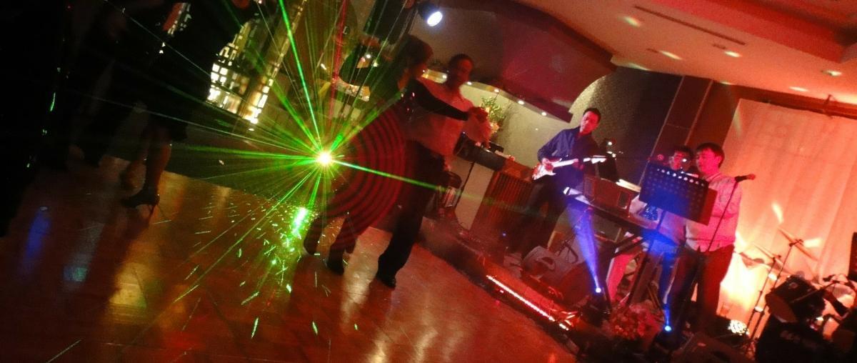 Tanzfläche mit Menschen, Band und Beleuchtung
