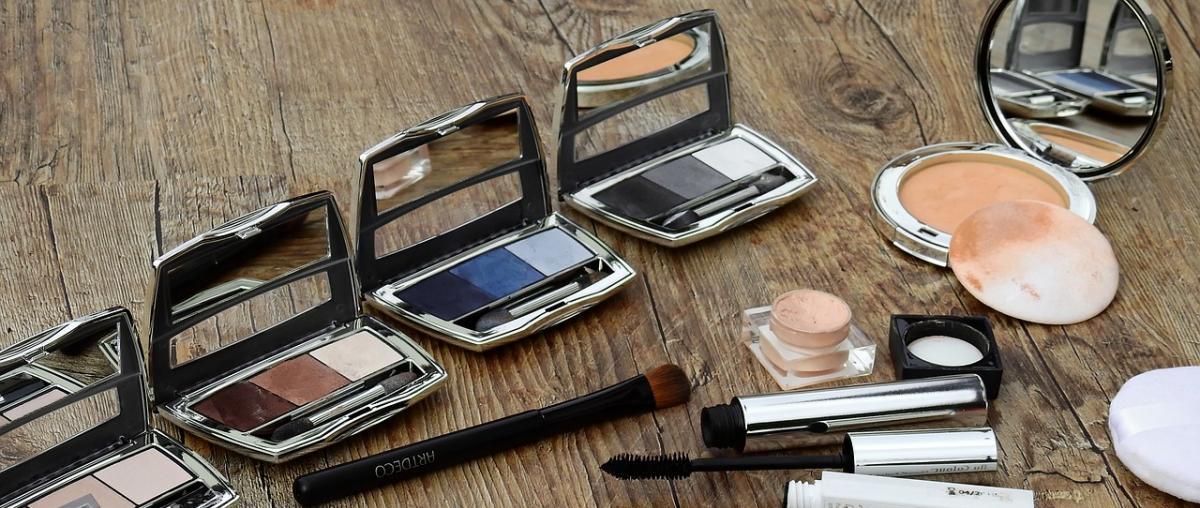 Verschiedene Make-Up Utensilien wie Wimpernstift, Pinsel, Rouge, Foundationfarben und Abschminkpads