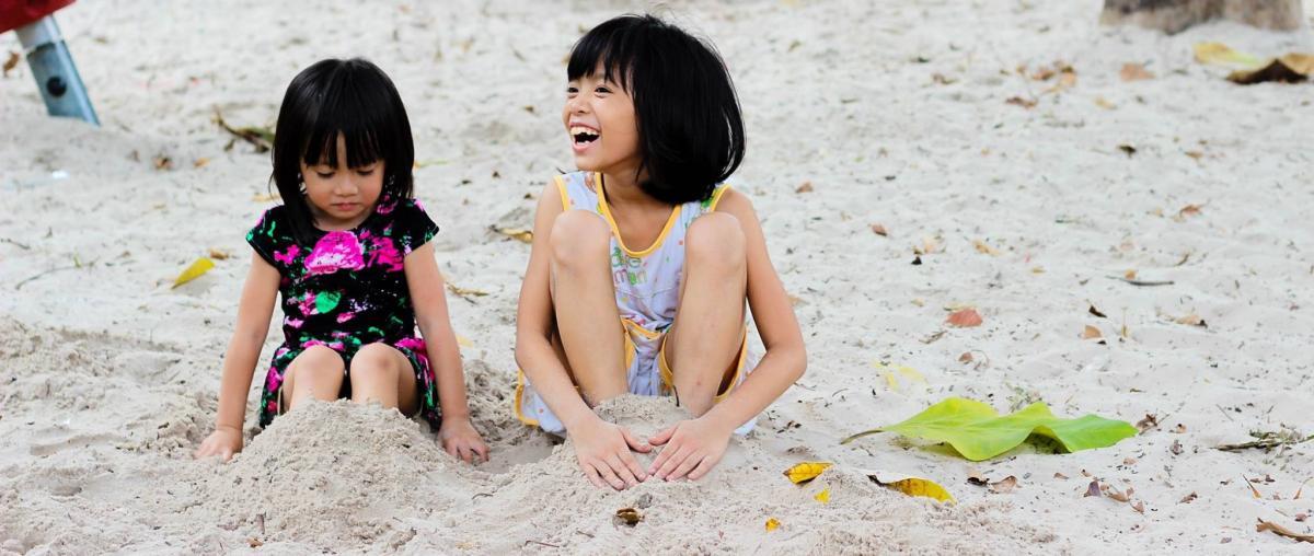 Zwei Mädchen spielen an einem Sandstrand im Schatten