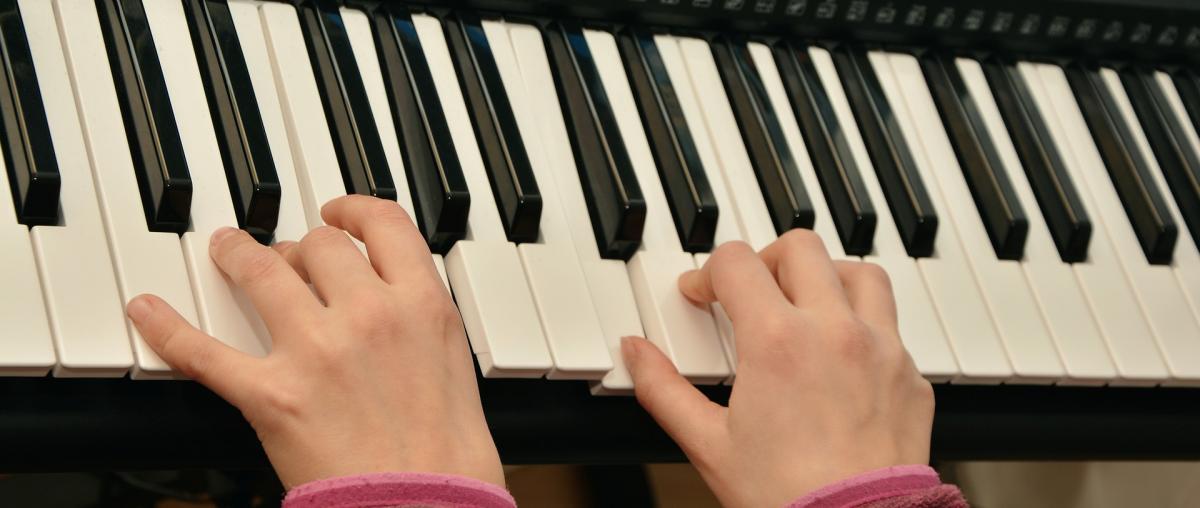 Kind spielt auf einem E-Piano mit vielen Funktionen und Einstellmöglichkeiten