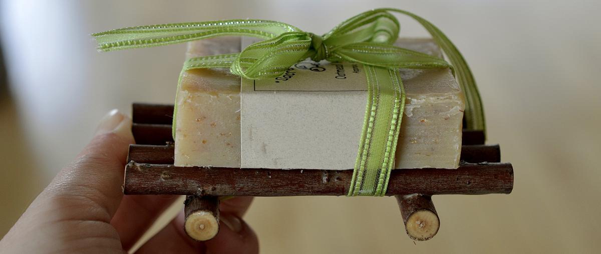 Ein Stück Naturseife mit einer grünen Schleife verpackt und auf einem kleinen Holzgestell als Geschenk dargereicht