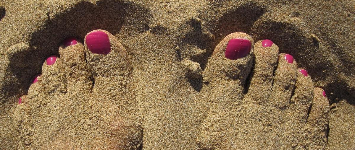 Füße mit leuchtend rotem Nagellack im Sand