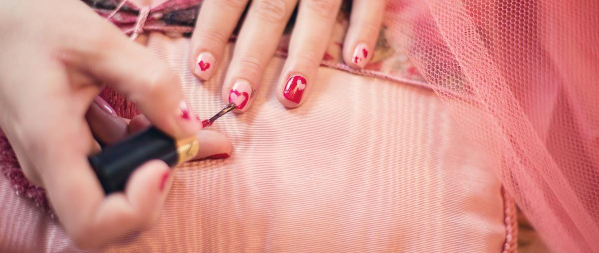 Nagellack wird benutzt, um Herzen auf Fingernägel mit einem Pinsel zu malen