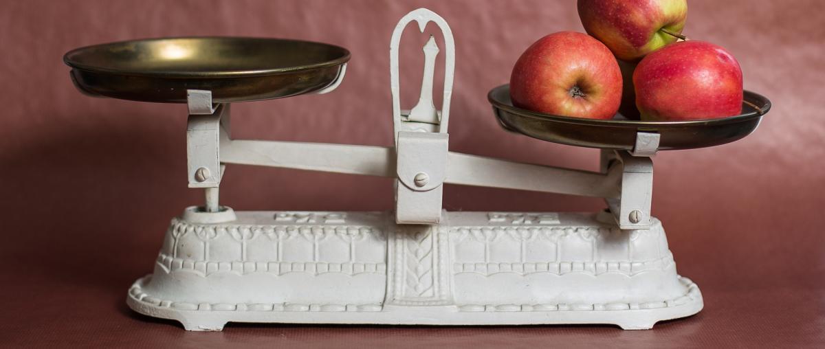 Weiße Balkenwaage wird zum Wiegen von Äpfeln benutzt