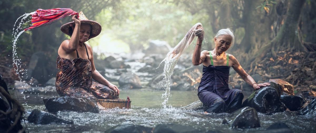 Zwei Frauen reinigen Wäsche in einem Fluss mit Steinen