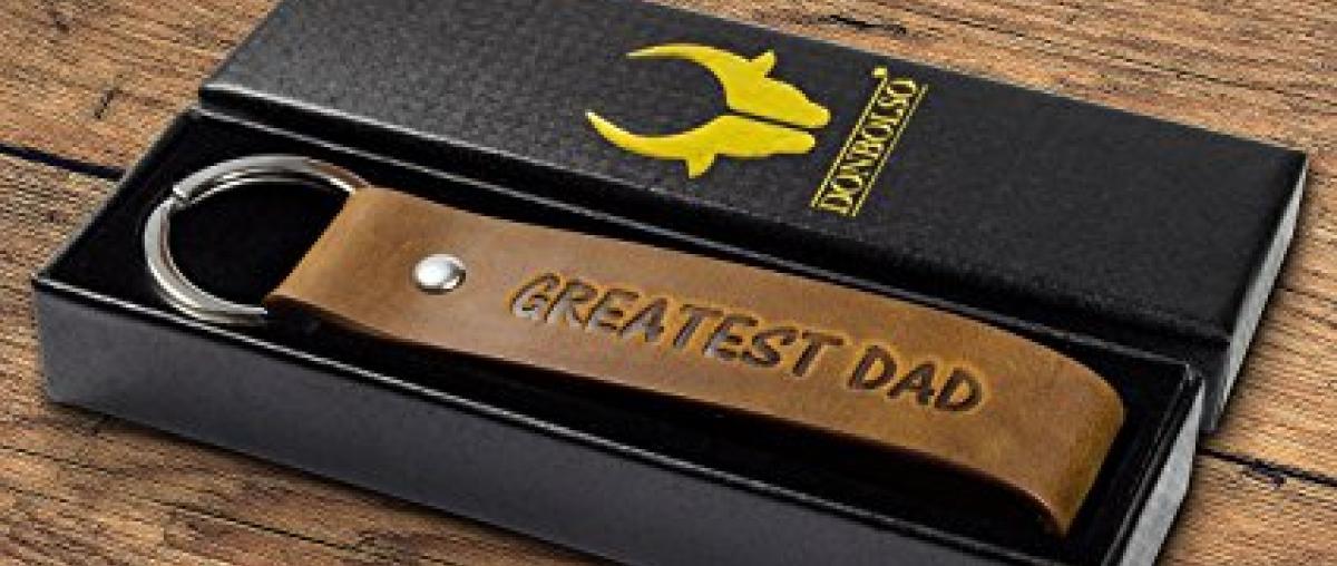 Schlüsselanhänger mit Lederband und der Aufschrift Greatest Dad in einer schwarzen Aufbewahrungsbox