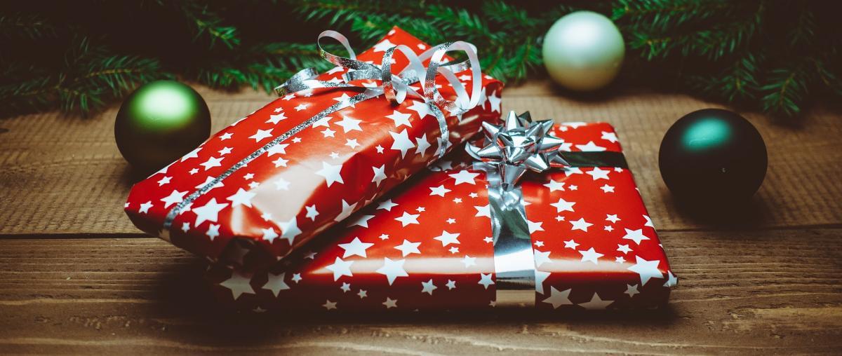 Verpackte Weihnachtsgeschenke in einem roten Geschenkpapier mit silbernen Sternen unter einem Weihnachtsbaum