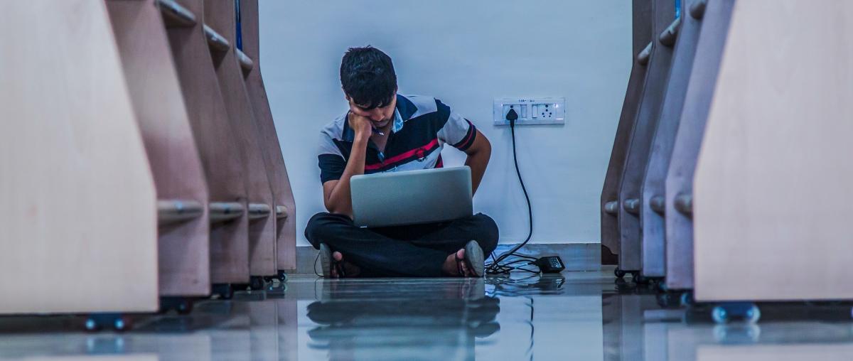 Junger Mann sitzt auf dem Boden einer Bibliothek im Schneidersitz und lernt am Notebook