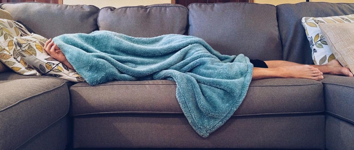 Mit einer türkisen Decke zugedeckte schlafende Person auf einem grauen und noch nicht ausgeklappten Schlafsofa im Wohnzimmer