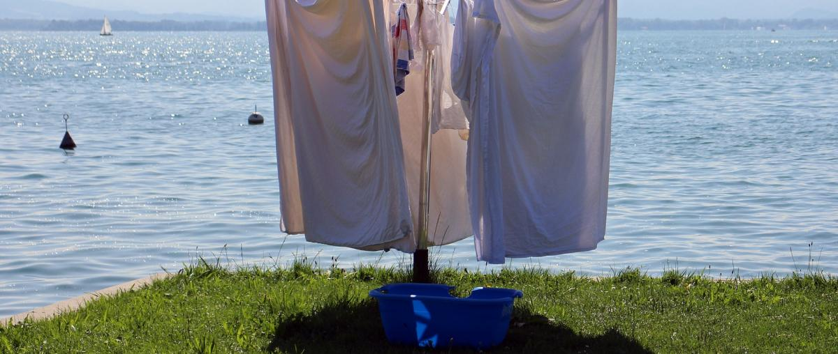 Wäschesspinne am Ufer in der Sonne, mit Wäsche bestückt und einem Wäschekorb der davor steht