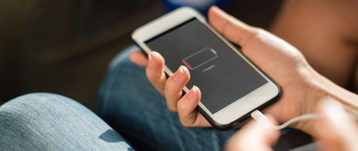 Der Akku eines Smartphone wird mit einem Ladegerät aufgeladen